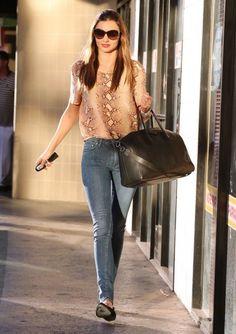 Miranda Kerr in snakeskin print blouse + pale skinny jeans + black flats. Easy errand running ensemble.