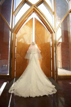 Bride standing in front of church doors back of dress view long lace train Essense of Australia Atlanta weddings Bel Fiore