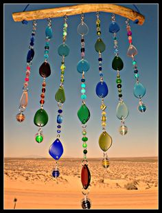 "This windchime consists of 16 silver chain link strands of tumbled stained glass and colorful glass beads. The strands have a different color glass hanging at the ends and coordinating colors of beautiful glass beads in between. The colors are greens, pink, amber, turquoise, blues, yellow, red, gold, orange and lavender. Hangs from a piece of driftwood that has been cleaned and treated. Measures 20"" in length at its longest. Width is approx. 13"" 