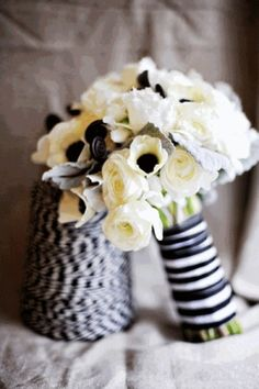Bouquet is filed with white anemones, white ranunculus, white roses, looped green bear grass, and gray dusty miller wrapped in black.