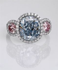 A natural fancy intense blue cushion-cut diamond is at the center of this handmade platinum ring, featuring round pink diamond side stones, all framed in white diamond accents.
