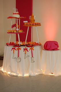 pink and orange wedding cake and cupcakes table