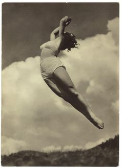 A woman from the 1940s seems to effortlessly and gracefully float in the air. The fluffy clouds in the background make this a dramatic and exciting photograph that will enliven any room or space. Arch