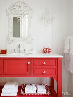 Don't be afraid to go bold with your bathroom color scheme. A bright red vanity shouts sophistication when paired with traditional accents like an ornate mirror, vintage chrome faucet, and sparkling wall sconces. Prevent a small space from becoming too busy by embracing loud color on a single item or wall./