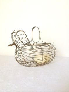 Vintage metal wire hen/chicken basket.  Handled basket for gathering eggs. Basket is not coated.  Handles fold up and down easily.  Minimal
