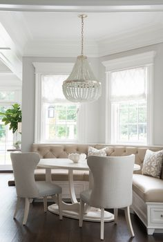 A stunning Currey & Co Chanteuse Chandelier hangs over a white oval dining table in a curved breakfast banquette.