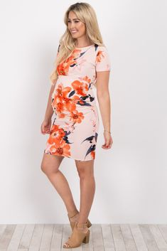 A floral print short sleeve fitted maternity dress. Ruched sides. Rounded neckline.