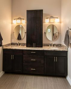 This master bathroom features a double sink vanity with dark brown wooden cabinets and neutral granite countertops. A convenient storage tower sits between the three-light fixtures and round mirrors that are positioned above each sink, while neutral floor tiles complete the look of the space.