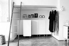 Small spaces: Custom closet using Ikea bookshelves - use Expedia shelves on wheels to create a custom wall unit
