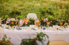 pretty tablescape with vintage glasses, river rocks, king proteas, gold animal figurines and more!