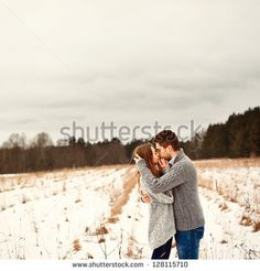 Outdoor sensual portrait of young beautiful couple in love posing in cold field covered with snow - stock photo