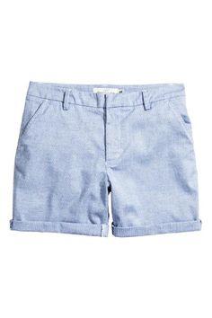 Short en coton tissé. Modèle avec braguette zippée et agrafe dissimulée. Poches latérales et poches passepoilées dans le dos.