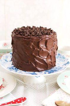 Tarta de chocolate sobre stand para tartas En este vídeo os muestro lo fácil que es hacer una tarta de chocolate rellena y cubierta con ganache. Solamente con un bol y una batidora de mano podemos hacer una mezcla muy chocolateada e irresistible. La podéis hornear en un sólo molde alto, pero con los moldes de layer cake podemos hacer directamente las capas del bizcocho en menor tiempo de horneado. Esto hace que el bizcocho no se reseque y tenga una jugosidad espectacular. La ganache es otra