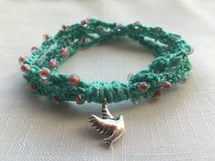 Turquoise and Coral Pink Beaded Crochet Bracelet with Dove Charm by Knitserenity on Etsy https://www.etsy.com/listing/262791641/turquoise-and-coral-pink-beaded-crochet