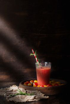 Glass of tomatoe juice - Tomato juice with rosemary, stick and tomatoes laying around with wooden background