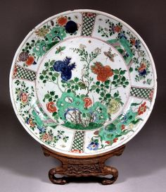 "A Chinese porcelain ""Famille Verte"" circular dish painted with flowers and butterflies, 13.625ins (346mm) diameter (painted leaf in underglaze blue to base - Kangxi period 1662 - 1722 - damaged) and carved wood stand for same"