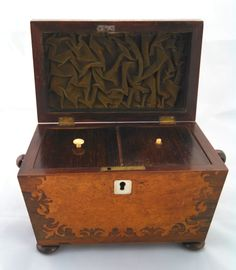 A mid to late 19th century wood tea caddy with two compartments and burl marquetry inlay on the front and hinged top. Each side of the caddy has a