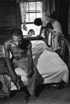 Tuberculosis case, 33-year-old Leon Snipe, sits morosely on bed while Maude arranges with his sister for him to go to state sanatorium.