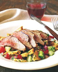 Lamb Fattoush | Tomatoes, cucumber, green pepper, and mint are tossed with torn and toasted pitas and topped with grilled butterflied leg of lamb for a delectable Middle Eastern salad. If you can't find a one-and-a-half-pound piece of leg of lamb, substitute lamb steaks and grill or broil them for about five minutes a side.