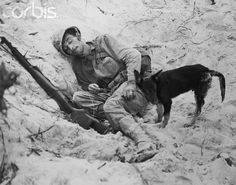 "Original caption:Warrior in Repose. Peleliu, Palau Islands: Exhausted by days of battle, an American Marine, unnamed, sleeps in a sandy hollow back of the front line on Peleliu Island. A Coast Guard combat photographer came upon the scene and snapped a scraggly black dog ""standing guard""."