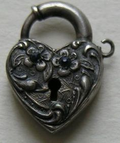 "This fun vintage (circa 1940) heart lock is one that can be a bit hard to find. The heart features two blue pastes set in flowers. The heart lock measures 11/16ths of an inch by 1/2 of an inch. The heart lock is in good working order and has a loop on which to attach a key if you have a spare. The back is marked sterling and is nice engraved with the letters ""W. J. V."" Condition is very good. by briana"