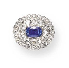 A BELLE EPOQUE SAPPHIRE AND DIAMOND BROOCH, BY MARCUS & CO. Set with a modified cushion-cut sapphire surrounded by old European-cut sapphires, within an old European-cut sapphire frame, mounted in platinum, circa 1910 Signed Marcus