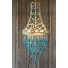 I see spray painting an old lamp shade frame, and gong to town with the tear drop crystals!  you could use anything from burlap twill tape to acrylic crystals to make the inter lacing top part, and use string, or rope lighting in the interior.  Or, yeah, you could buy this from Bellacor too..