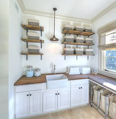 Cottage laundry room features stacked rustic shelves with brackets flanking cage pendant light over small farmhouse sink and white cabinets accented with reclaimed wood countertops. Laundry Room Shelves, Laundry Room Cabinets, Laundry Room Organization, Laundry Room Design, Laundry Rooms, Small Laundry, Mud Rooms, Basement Laundry, Laundry Bags