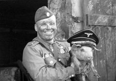 Russian soldier holding a pig.