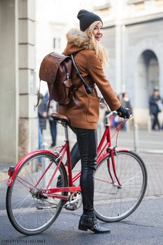 Petra Terešak wearing leather leggings and croped jacket, riding red bike