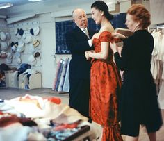 The legendary Christian Dior fitting a dress on one of his models