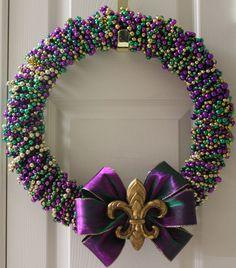 Door Wreath Tutorial ~ Now I know what to do with all those old Mardi Gras beads! I could see myself making a small wreath for the house - love the fleur de lils and purple bow - great colors!