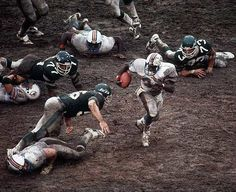 Dolphins running against the Jets on a muddy field in Miami
