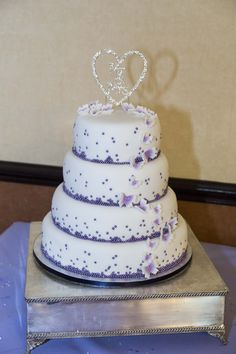 4 tier white Wedding cake with purple touches to match the colour scheme of your day.