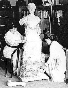 Dressing a first lady mannequin, Arts and Industries Building, 1915  Cassie Julian-James (left) and Rose Gouverneur Hoes (right), founders of the Smithsonian's First Ladies Collection, dress a mannequin in a gown worn by Louisa Catherine Adams, wife of President John Quincy Adams. Part of the National Museum's historic costume exhibition, the mannequin, trimmed with a pair of white satin slippers, was displayed inside a glass case with another mannequin represe