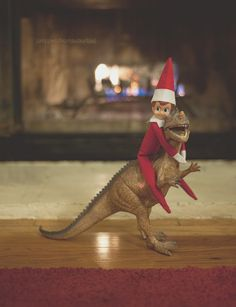Elf on the shelf rides a dinosaur