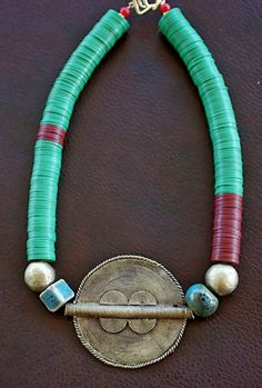 A new addition to the Tribal Fusion collection. Green and red vinyl beads are accented by handmade porcelain beads. The highlight of the neck art are handmade heavy metal beads and a 8 cm African Wax Bead pendant.  Available at http://www.facebook.com/Jewelry.by.RuHH