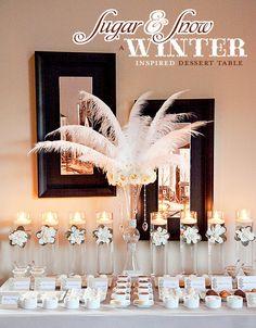 Mesa de postres decorada con velas y plumas.