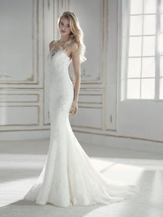 Elegant, sensual and romantic. This low waist mermaid wedding dress with a bodice decorated with illusions fits the figure like a glove. A design that stylizes the silhouette and accentuates the bride's femininity with illusions and a satiny effect, lace, and embroidered tulle with beading. A dress as unique as the bride who wears it.