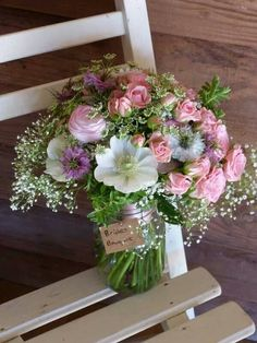 White anemones, pink roses, lilac nigella and ammi majus in a handtied bouquet, grown and arranged by sussex cutting garden