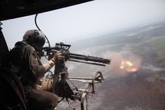 "A helicopter door gunner firing an M134 7.62×51mm NATO caliber ""Minigun"" in Vietnam, a hydraulically or pneumatically driven, six-barrel, air-cooled, electrically-fired Gatling-style rotary cannon which fires rounds at an extremely high rate, typically 6,000 rounds per minute."