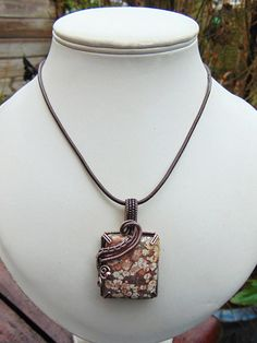 Made from a beautiful ocean jasper cabochon this wire wrapped pendant makes an unusual statement. The stone has floral patterns across the face and Ive prong set it to make the most of these unique markings. A patina has been applied to the copper to give it more depth and it will