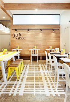 Inspiring Interior in a Fish Market with fresh yellow details | Sillas Marine Pet en plástico blanco para mobiliario de mesas.