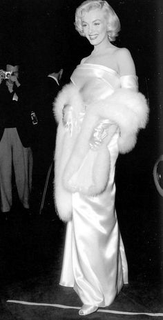 "Marilyn is breathtaking in this sleek white satin strapless dress, belted at the waist by Travilla, worn with white fox stole, for the premiere of ""Call me Madam"" on March 25, 1953 