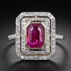 A rare, radiant red emerald-cut ruby - weighing 2.20 carats - and accompanied by an AGL certificate which states: no heat enhancement and Burmese origin - glistens and glows from within sparkling concentric frames of teeny-tiny old mine-cut diamonds in this ravishing, original Edwardian-era ring from the turn-of-the twentieth century. Finely handcrafted in platinum over 18 karat yellow gold; just shy of 5/8 inch long by 1/2 inch wide.