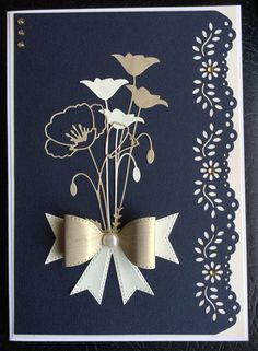 By Dianne Potter:Identical layout to my original card (done in yellow and grey)this time in cream,dull gold and dark navy blue.Memory Box Prim and Perky Poppy dies,Sue Wilson for Creative Expressions Classic Bow die and Martha Stewart floral punch