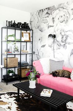 black shelving unit with black sconces, pink sofa and mural wallpaper