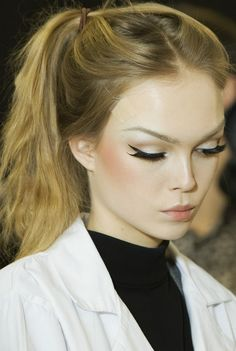 Soft makeup with clean black liner and structured brow. half lashes. nude lips, peach blusher. soft pony. classic.