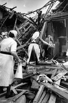 Nurses climb through the rubble at Farringdon Market, London after a rocket had fallen on it during the last months of WW II. Original Publication: Picture Post - 1967 - One Story We Couldn't Tell - pub. 2 October 1948