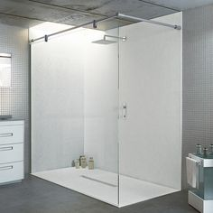 This large statement walk-in shower has been created in a modern warehouse style apartment using a Nature White coloured slate effect Privilege ultra-thin 20mm shower tray with matching shower wall paneling and a frameless fixed shower screen